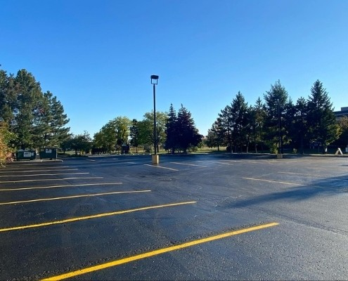 Image depicts freshly painted parking lines in a commercial parking lot.