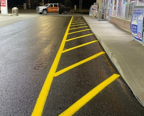 Image depicts freshly painted traffic lines at a gas station.
