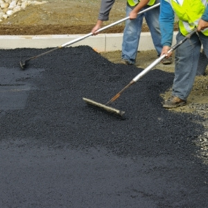 Image depicts two of our experts paving a commercial asphalt driveway.