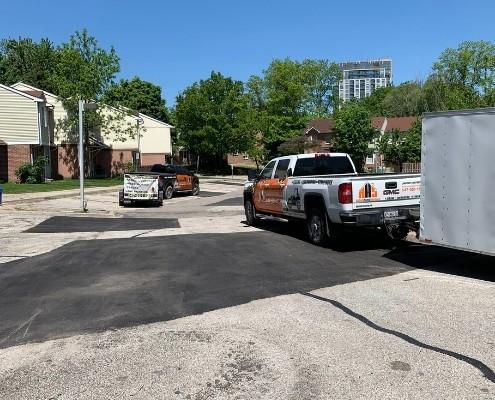 Image depicts two asphalt sealing service trucks.