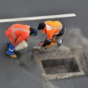 Image depicts two of our experts repairing a catch basin in a commercial driveway.