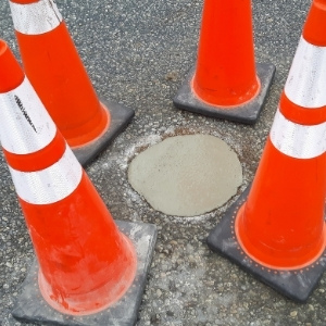 Image depicts a pothole in a commercial driveway.