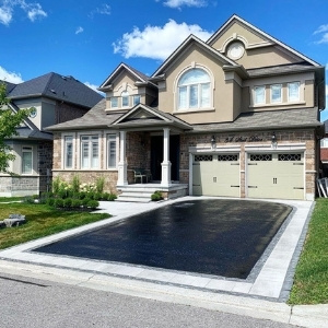 Image depicts a home with a driveway that has been recently sealed.