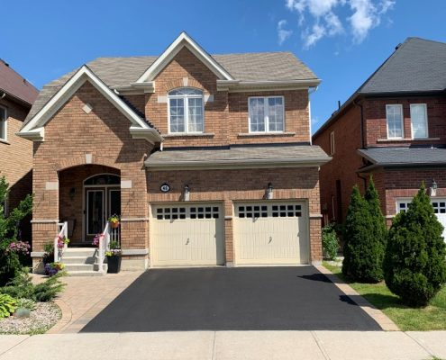 Image depicts a home in Vaughan, Ontario with a driveway that has been sealed.