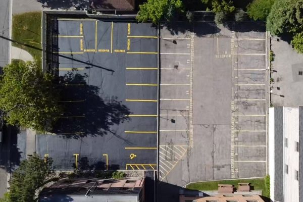 Image depicts a commercial parking from a recent asphalt sealing and line painting project by AHS.